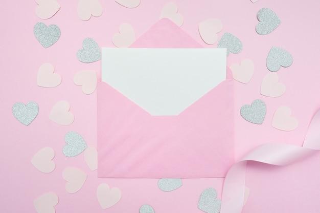 Пустой розовый конверт с белым листом бумаги