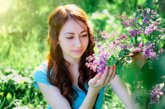 Молодая женщина возле куста сирени в весеннем парке