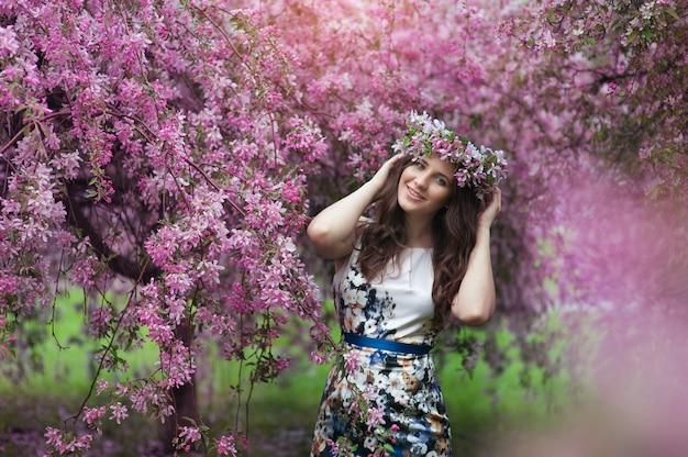 Счастливая молодая женщина с венком на голове в цветущем весеннем саду