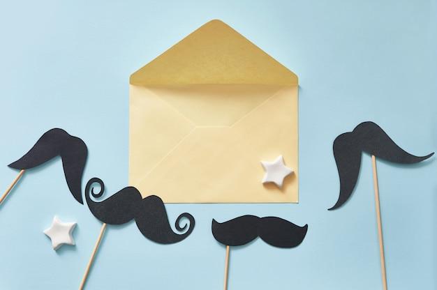 Макет черные усы на синем фоне бумаги и желтый конверт