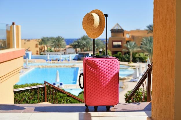 旅行、夏の休日、休暇の概念。帽子とピンクのスーツケース