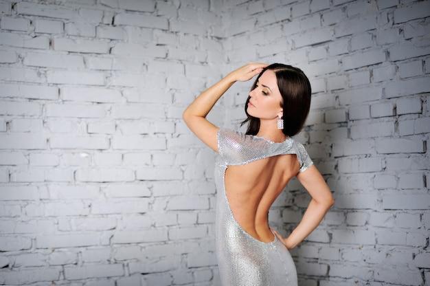 オープンバックのドレスでポーズ美しい高級女性モデル。ファッションイブニングメイク