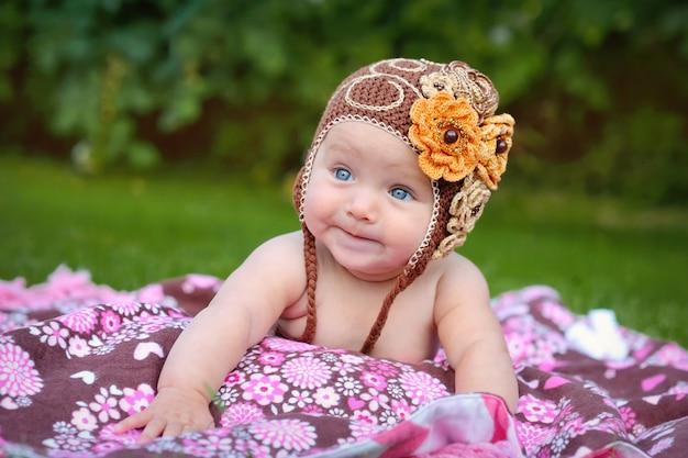 Милый ребенок ползет на улице в коричневой вязаной шапке