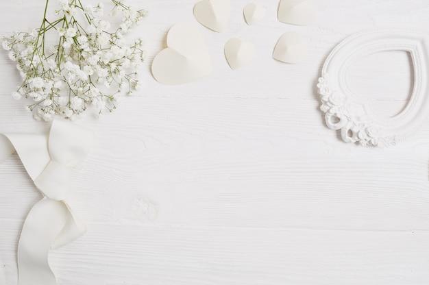 花とグリーティングカード聖バレンタインの日の紙のハートのモックアップの背景