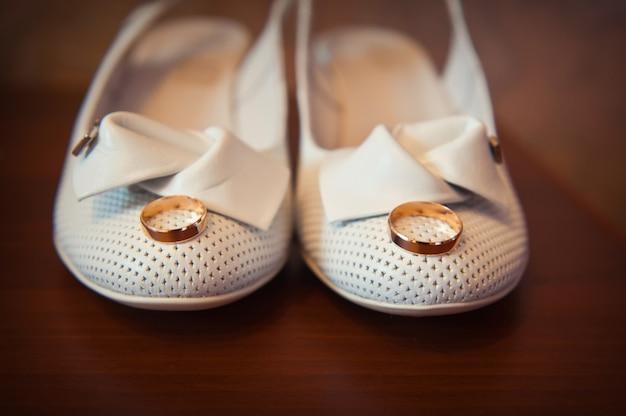 Золотое кольцо на белых туфлях невесты крупным планом