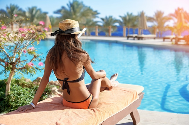 豪華な夏のプールの近くのデイベッドでリラックスした麦わら帽子の女性