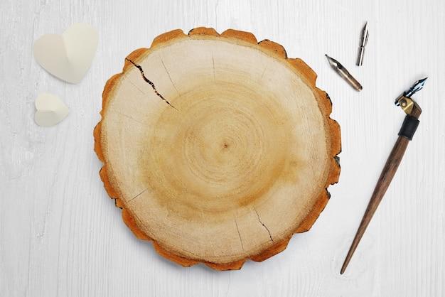 ホワイトペーパーハートと木製の円に近い書道の羽