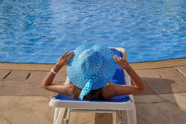 Женщина в шляпе отдыхает на шезлонге на краю бассейна летом на открытом воздухе
