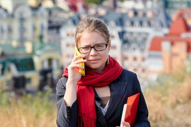 街の背景にメガネの女性は電話で