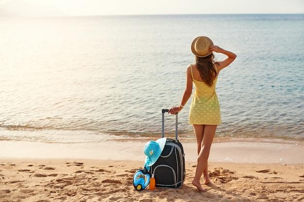 Красивая молодая женщина в шляпе стоит с чемоданом на прекрасном море