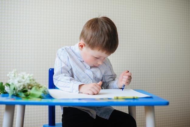 机に座っている少年を描画します