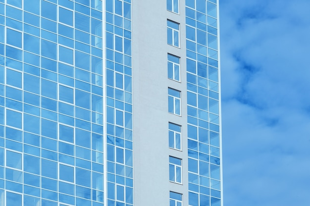 Многоэтажное стеклянное офисное здание на фоне неба