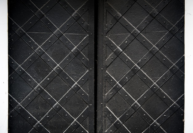 背景のリベットと黒の古い金属製のドアのテクスチャ