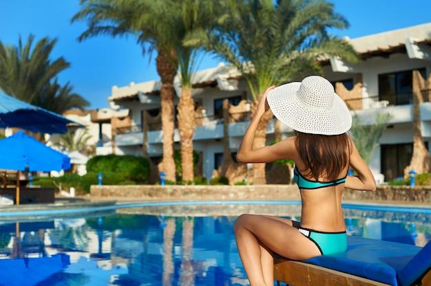 スイミングプールのそばのサンラウンジャーに座って帽子旅行の概念時間の若い女性