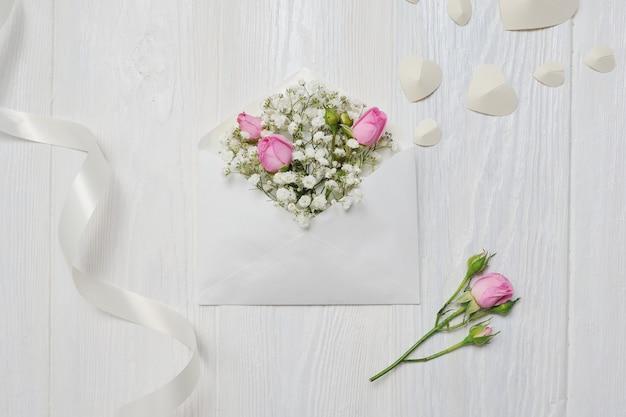 あなたのテキストのための場所で素朴なスタイルで聖バレンタインデーのバラとモックアップの手紙、フラットレイアウトトップビュー