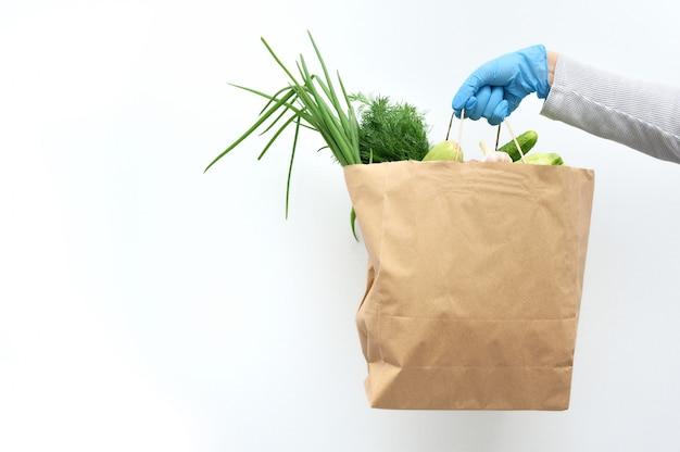 Волонтер в синих перчатках держит в руках пакет пожертвований овощей, чтобы помочь бедным. ящик донат