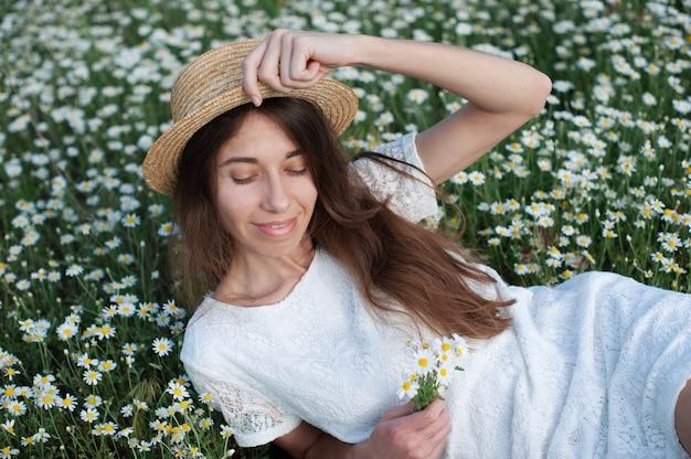 カモミールフィールド、きれいな女の子の花の草原に横たわっている素敵な女性を楽しむ美しい女性