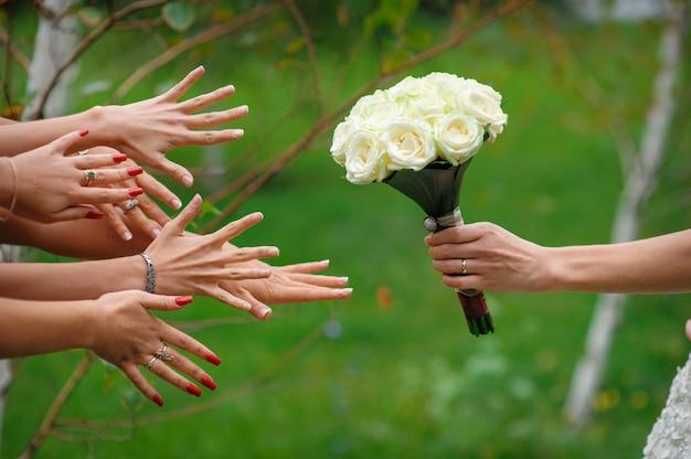 花嫁は美しいウェディングブーケを伸ばします