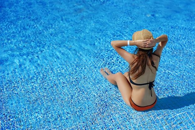 Женщина в соломенной шляпе отдыхает на шезлонге возле роскошного летнего бассейна в отеле, концепция время путешествовать