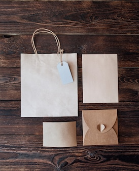 Макет бумажный пакет из крафт-бумаги с подарочной биркой и новогодними подарочными коробками на деревянном фоне