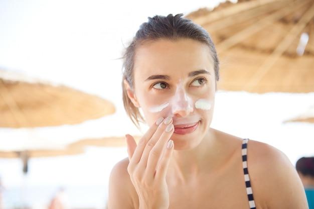美しい女性は保護のためにビーチで顔の日焼け止めを塗る