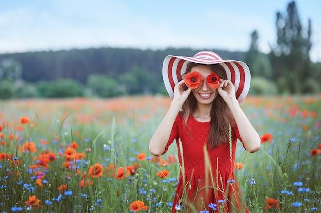 彼女の目の前に赤いケシを保持していると花の牧草地に立っている美しい若い女性