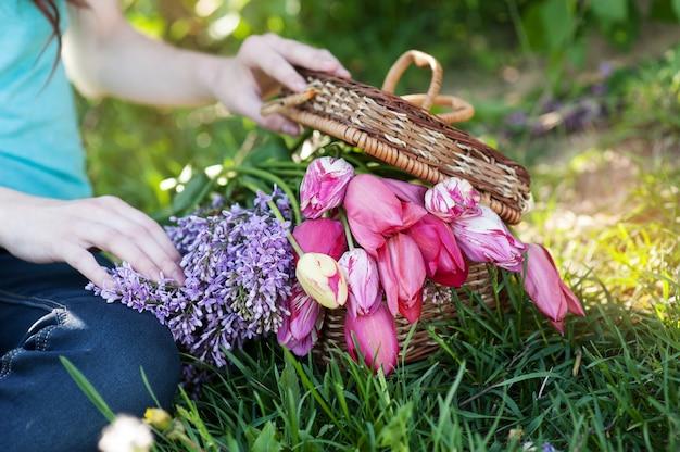 わらのバスケットにチューリップとライラックの花束