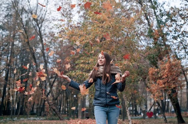 Счастливая красивая девушка, подбрасывая листья в воздухе в осеннем парке