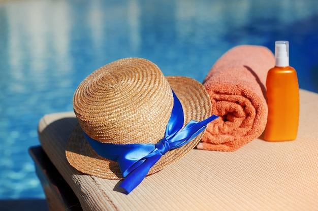 オレンジ色の綿のタオルと日焼け止めボディローションとオレンジ色のチューブの帽子