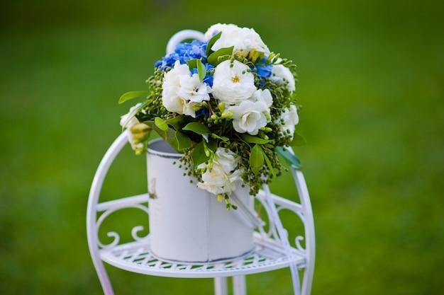 装飾的な金属製のスタンドにバラのアジサイの花束