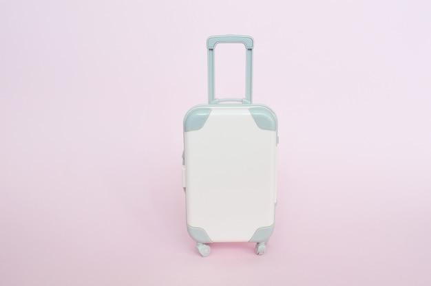 Стильный чемодан на розовом фоне