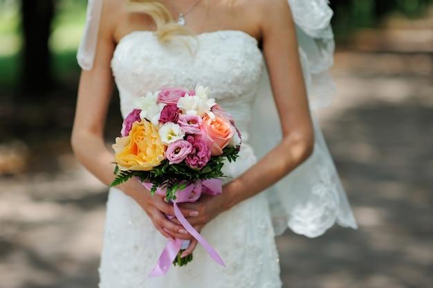 花嫁はバラと美しいウェディングブーケを保持