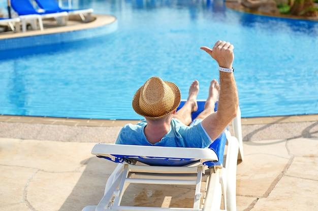 ホテルでサンラウンジャーに横になっている若いと成功した男