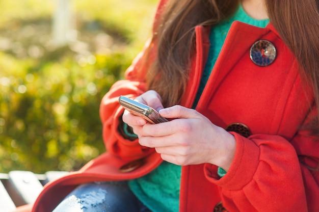 彼女の携帯電話と通りのベンチに座っていると幸せな女のテキストメッセージ