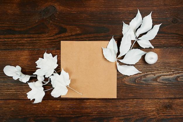 紙の平らな空のクラフトシートはあなたの芸術、写真または手レタリング組成コピースペース、トップビューのためにモックアップを置きます。暗い茶色の木製の背景に白い葉で作られた秋の組成