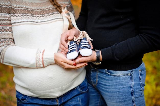 妊娠中の女性が夫を抱き締めると、胎児のためのブーツを保持します