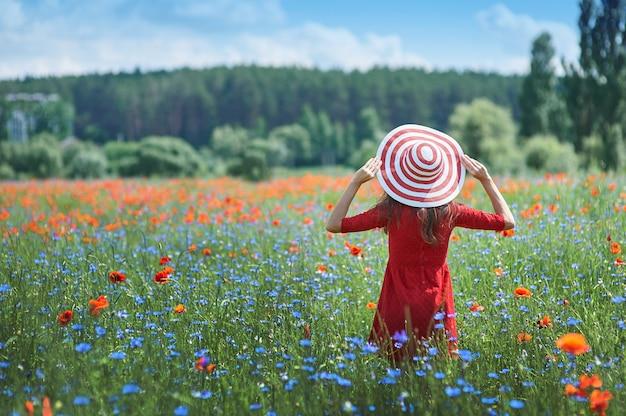 赤いドレスと大きな赤い縞模様の帽子の夢のような女性が美しいハーブで引き返した