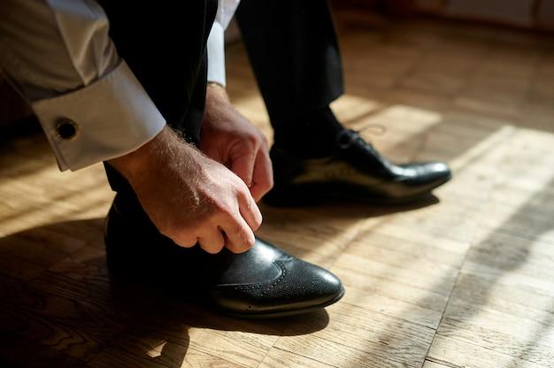 床に靴ひもを結ぶビジネス男