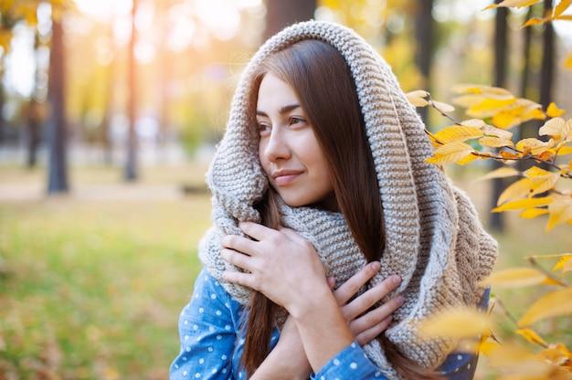 黄色の秋の公園を歩いてかわいい笑顔の女性。