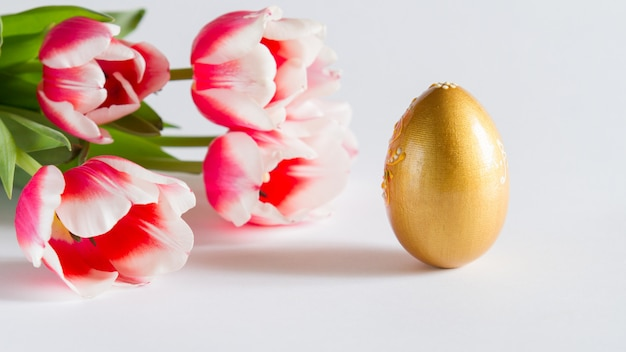 Красивая пасхальная открытка, фон с цветами и золотое яйцо