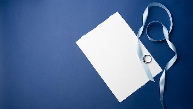 招待状、挨拶用のテンプレート。青色の背景、白い紙、封筒、ノート、石のある指輪、装飾キャンドル。結婚式、誕生日のミニマルなデザイン。