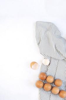 しわストライプナプキン、具体的な白い背景に生の生卵。