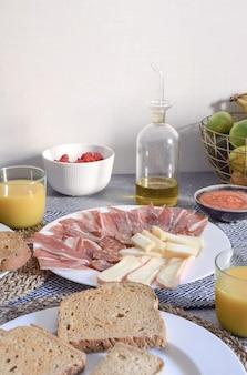 伝統的なスペインの朝食ハモンチーズトーストしたパントマトオリーブオイルオレンジジュースコピースペース