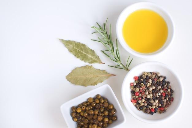 Фарфоровая тарелка с оливковым маслом розмариновая ветвь перец микс лавровый лист