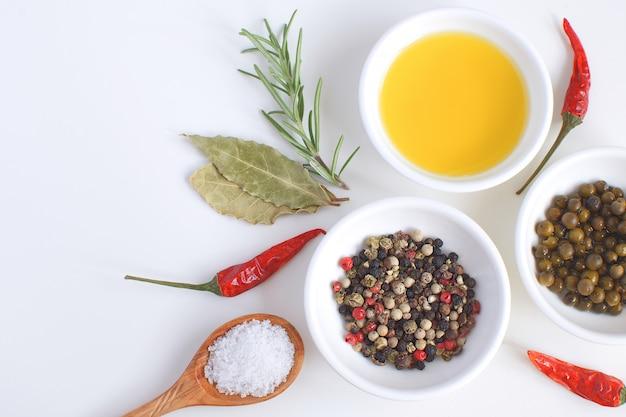 Фарфоровая тарелка с оливковым маслом розмариновая ветвь перец микс чили лавровый лист