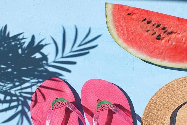 新鮮なスイカフリップフロップ麦わら帽子水色の背景トップビューコピースペース