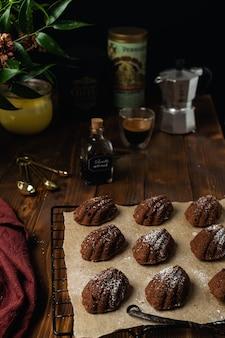 Домашняя выпечка шоколадное печенье мадлен на охладительной решетке с ингредиентами и посудой на деревенском деревянном