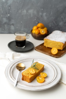 新鮮なキンカンとローズマリー、木製のまな板、エスプレッソコーヒーで飾られたオレンジのケーキを提供しています