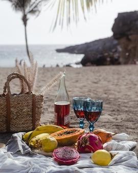 バラのワインと新鮮な果物と夕日のビーチでのピクニック