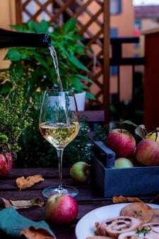 素朴な木製のテーブルに白ワインまたはサダーグラス